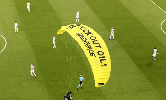 The German players look on as a Greenpeace paraglider lands in the stadium prior to the Euro 2020 soccer championship group F match between France and Germany at the Allianz Arena stadium in Munich, Germany, on June 15, 2021. (ctivist Alexander Hassenstein/Pool via AP)