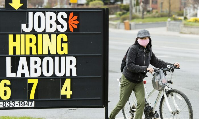 A woman checks out a job advertisement sign in Toronto on April 29, 2020. (The Canadian Press/Nathan Denette)