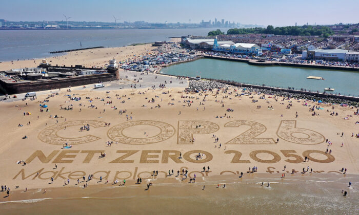 A giant sand art work adorns New Brighton Beach to highlight global warming and the forthcoming Cop26 global climate conference in the Wirral, Merseyside, on May 31, 2021. (Christopher Furlong/Getty Images)
