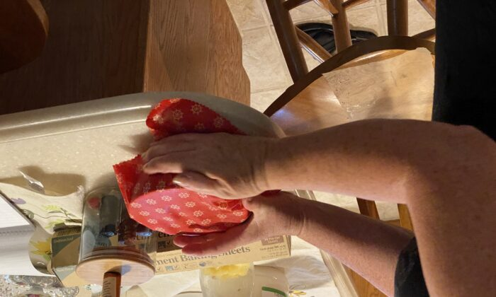 Tressa Hoffman tests a newly made beeswax wrap on a bowl. The warmth of her hands helps mold the beeswax wrap on top of the bowl.(Tamara Browning)
