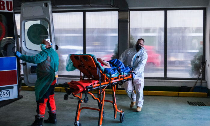 Paramedics wheel a stretcher with a patient showing COVID-19 symptoms from a nursery house in Bochnia, Poland, on Dec. 1, 2020. (Omar Marques/Getty Images)