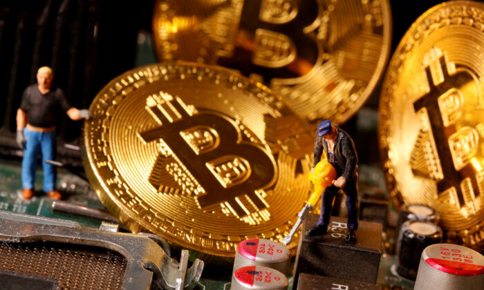 A representation of virtual currency bitcoin and small toy figures are placed on computer motherboard in this illustration taken on Jan. 7, 2021. (Dado Ruvic/Reuters)