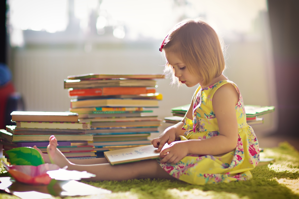 A,Little,Cute,Girl,In,A,Yellow,Dress,Reading,A