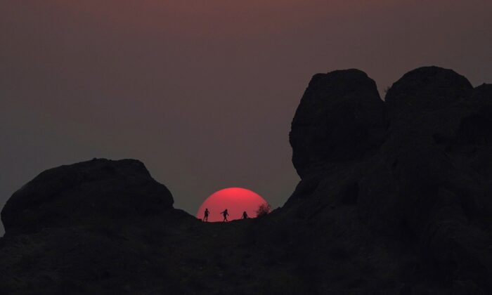 Hikers pause to watch the sunset at Papago Park during a heatwave where temperatures reached 115-degrees, in Phoenix, Arizona, June 15, 2021. (Ross D. Franklin/AP)