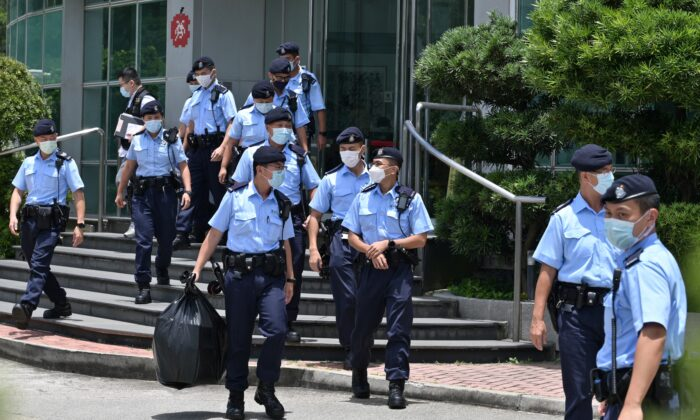 Police officers leave the Apple Daily newspaper offices in Hong Kong after a raid by over 500 officers on June 17, 2021. (Anthony Wallace/AFP via Getty Images)