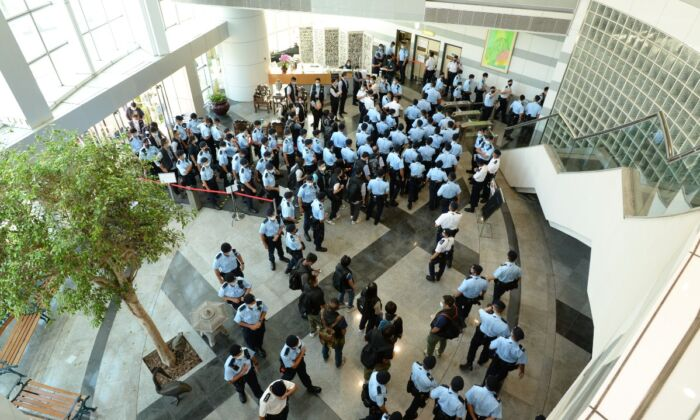 In this handout image provided by Apple Daily, police officers conduct a raid at the Apple Daily office in Hong Kong, China, on June 17, 2021. (Apple Daily via Getty Images)