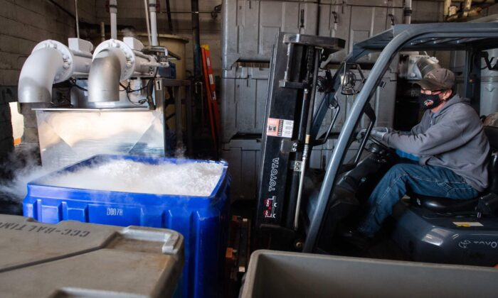 An employee at Capitol Carbonic, which makes dry ice used by the pharmaceutical industry, uses a forklift to move a cooler of dry ice pellets in a warehouse in Baltimore, Maryland, on Nov. 20, 2020. (Saul Loeb/AFP/Getty Images)