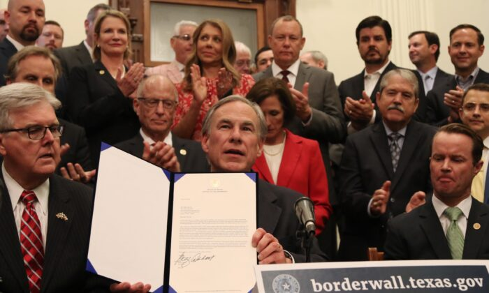 Texas Governor Greg Abbott shows off a bill he signed during a press conference at the state capitol in Austin, Texas, on June 16, 2021. (Mei Zhong/The Epoch Times)