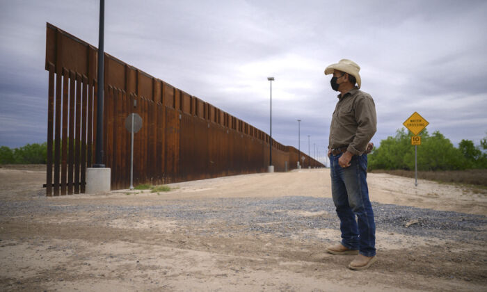 A ranch owner stands before a portion of the unfinished border wall that former U.S. president Donald Trump tried to build, near Roma, Texas, on March 28, 2021. (Ed Jones/AFP via Getty Images)