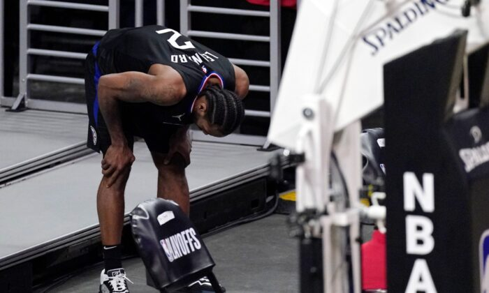 Los Angeles Clippers forward Kawhi Leonard holds his knee after stepping awkwardly during the second half in Game 4 of a second-round NBA basketball playoff series against the Utah Jazz , in Los Angeles, Calif., on June 14, 2021. (Mark J. Terrill/AP Photo)