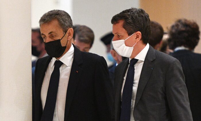 Former French President Nicolas Sarkozy (L) walks during a hearing of the so-called Bygmalion case trial which sees him charged with illicit financing for his failed 2012 re-election campaign, in Paris, France, on June 15, 2021. (Christophe Archambault/AFP via Getty Images)