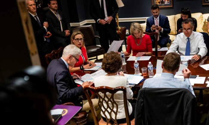 (L-R) U.S. Sen. Bill Cassidy (R-LA), U.S. Sen. Kyrsten Sinema (D-AZ), U.S. Sen. Lisa Murkowski (R-AK), and U.S. Sen. Mitt Romney (R-UT) hold a bipartisan meeting on infrastructure in the basement of the U.S. Capitol building after original talks fell through with the White House in Washington on June 8, 2021. (Samuel Corum/Getty Images)