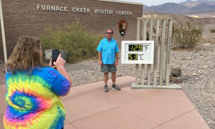 Patrick Fox, 63, from Utah poses for a picture next to the thermometer at the Furnace Creek Visitor Center at Death Valley National Park, with the temperature showing at 129 degrees Fahrenheit (53.8 degrees C) in Death Valley, Calif., on June 16, 2021. (Norma Galeana/Reuters)
