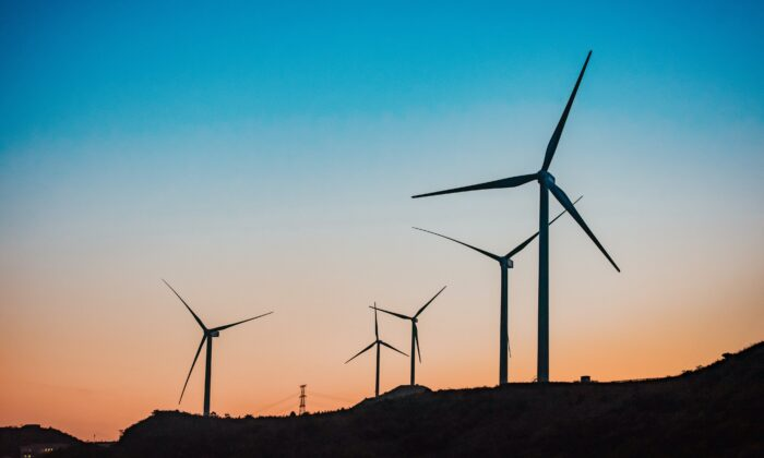 Wind turbines in twilight. (Unsplash)