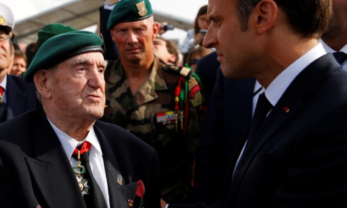 French President Emmanuel Macron listens to French war veteran Leon Gautier, a member of the Kieffer commando, during a D-Day commemoration ceremony in memory of marines and the famed Kieffer commandos who took part in D-Day landings, in Colleville-Montgomery, France, on June 6, 2019. (Francois Mori/Pool via Reuters)