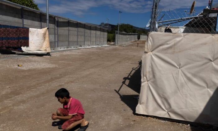 A boy plays next to a newly built concrete wall inside the Ritsona camp for refugees and migrants, in Greece, on June 15, 2021. (Alkis Konstantinidis/Reuters)
