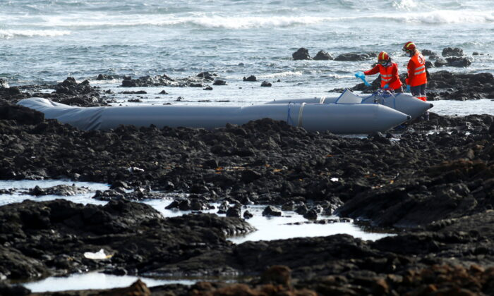 Rescue workers search for bodies after a boat with 46 migrants from the Maghreb region capsized in the beach of Orzola, in the Canary Island of Lanzarote, Spain, on June 18, 2021. (Borja Suarez/Reuters)
