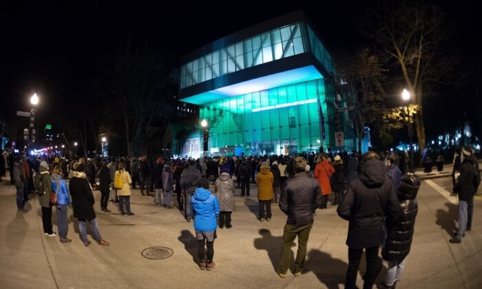 People gather at the Quebec National Museum in a vigil to honour Francois Duchesne who was stabbed to death on Halloween night by a man with a sword, on Nov. 3, 2020 in Quebec City. (The Canadian Press/Jacques Boissinot)