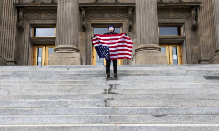 A student holding a U.S. flag upside down stands atop the steps at the Idaho Capitol building in Boise on April 26, 2021. The Idaho Senate has approved legislation aimed at preventing schools and universities from indoctrinating students through teaching critical race theory. (Darin Oswald/Idaho Statesman via AP)