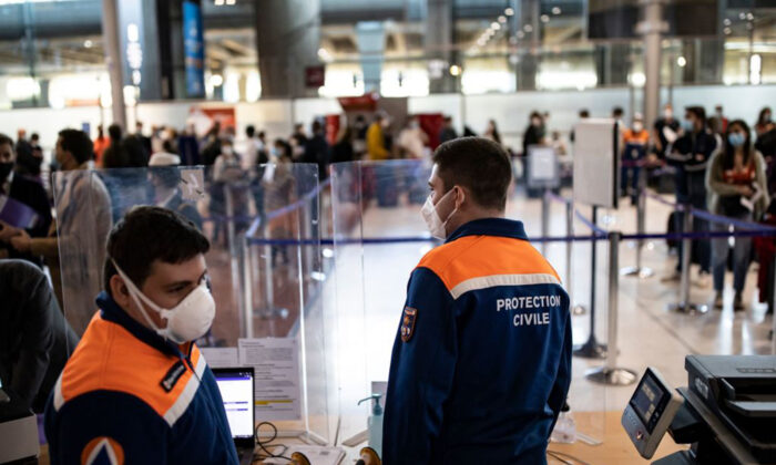 Members of the Civil Protection man a COVID-19 control point where passengers from specific countries register for COVID-19 tests upon their arrival at Roissy Charles de Gaulle airport in Roissy near Paris, France, on April 25, 2021. (Ian Langsdon/Pool/AFP via Getty Images)