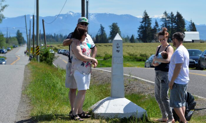 Daniel and Cheryl Sanchez, of Seattle, Washington, introduce their two week old baby to grandparents Rosemary and Roland Berezan of Surrey, during a roadside meet up along the Canada-U.S. border, closed to non-essential travel due to the coronavirus disease (COVID-19) restrictions as the family gathered for Mother's Day in Langley, British Columbia, Canada, on May 10, 2020.  (Jennifer Gauthier/Reuters)