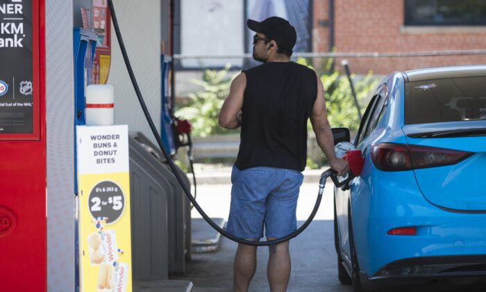 A commuter pumps gas into their vehicle at a Esso gas station in Toronto, Canada, on June 15, 2021. (Tijana Martin/The Canadian Press)