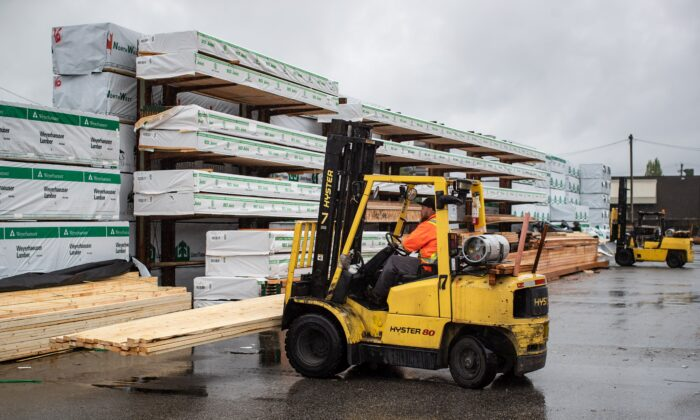 A worker uses a forklift to move lumber at Haney Builders' Supplies in Maple Ridge, B.C., on June 12, 2020. (The Canadian Press/Darryl Dyck)