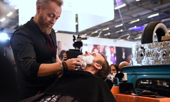 """A barber shaves former French Economy Minister and founder of the political movement """"En Marche"""" (On the Move), now president of France, Emmanuel Macron during a visit to the International Hairdressing Show (Salon International de la Coiffure) in Paris on Sept. 12, 2016.  (Eric Feferberg/AFP via Getty Images)"""