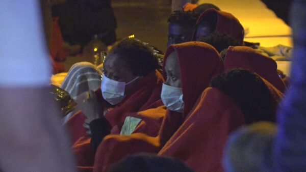 Migrants sit after being rescued
