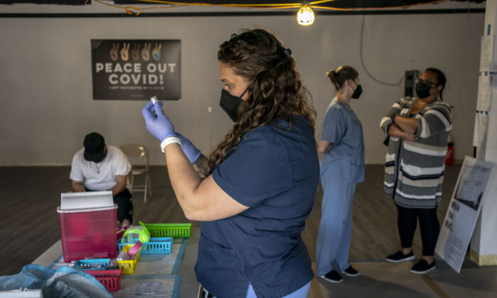 Nurse practitioner Nicole Warner prepares doses of COVID-19 vaccines during the Joints4Jabs COVID-19 vaccination clinic at the Uncle Ikes White Center cannabis shop in Seattle, Wash., on June 16, 2021. (David Ryder/Getty Images)