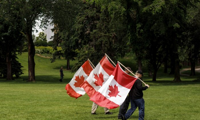 People carry Canadian flags through a park in Edmonton to celebrate Canada Day on July 1, 2020, when most celebrations were moved online due to the pandemic. (The Canadian Press/Jason Franson)