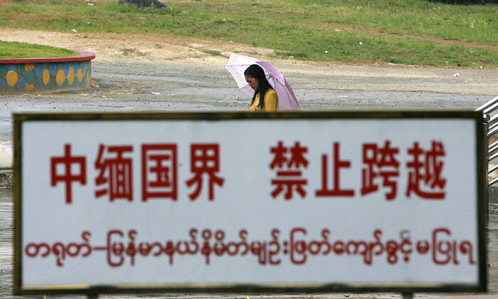 A Burmese woman walks behind a warning sign along the boundary line in the China-Burma border town of Wanding, in China's southwestern province of Yunnan, on Sept. 27 2007. (STR/AFP via Getty Images)