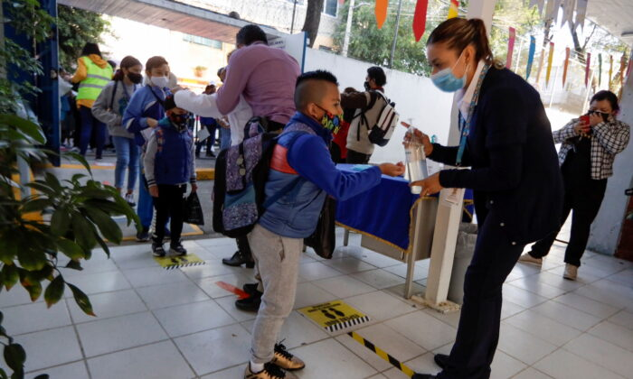 A child receives hand sanitizer while arriving at the Ignacio Zaragoza elementary school as Mexico City's authorities resumed in-person classes after a downward trend in the number of infections and hospitalizations of the coronavirus disease (COVID-19), in Mexico City, Mexico, June 7, 2021. (Luis Cortes/Reuters/File Photo)