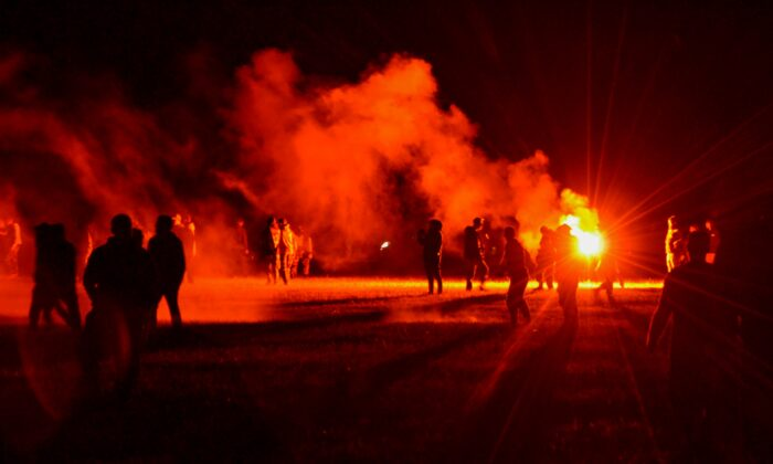 Youths stand in a field during clashes as police tried to break up an unauthorized rave party near Redon, Brittany, on June 18, 2021. (AP Photo)