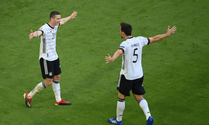 Germany's Robin Gosens (L) celebrates Germany's Mats Hummels after scoring his side's fourth goal during the Euro 2020 soccer championship group F match between Portugal and Germany at the football arena stadium in Munich, Germany, on June 19, 2021. (Matthias Hangst/Pool Photo via AP)