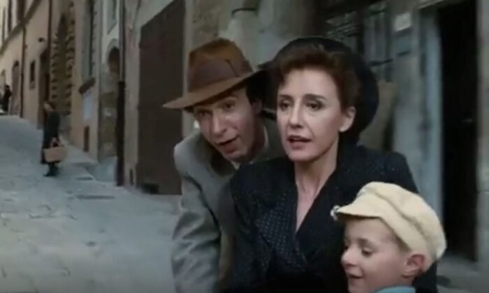 """""""Life Is Beautiful"""" starts as a tale of merry courtship and happy family life, starring (L–R) Roberto Benigni, Nicoletta Braschi, and Giorgio Cantarini. (Miramax Films)"""