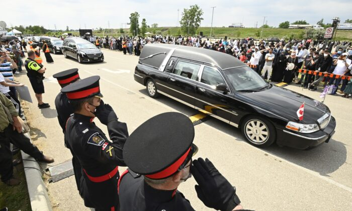 Police officers salute as hearses pass during the funeral for four Muslim family members killed in a deadly vehicle attack, in London, Ont., on June 12, 2021. Nathaniel Veltman, the driver of the vehicle, is facing terrorism charges. (The Canadian Press/Frank Gunn)