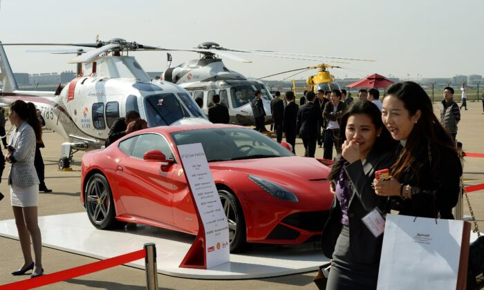 People walk past a Ferrari and helicopters during the Asian Business Aviation Conference and Exhibition at the Shanghai Hongqiao International Airport on April 14, 2014. (Mark Ralston/AFP via Getty Images)
