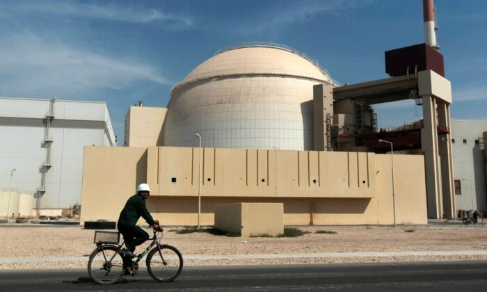 A worker rides a bicycle in front of the reactor building of the Bushehr nuclear power plant, just outside the southern city of Bushehr, Iran, on Oct. 26, 2010. (Mehr News Agency/Majid Asgaripour/AP Photo)