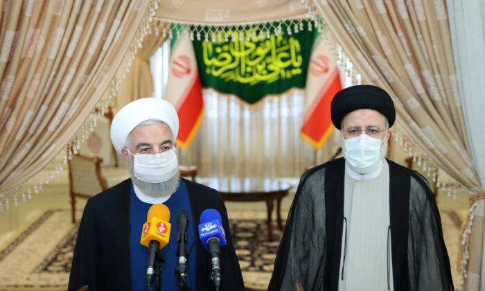 Iran's outgoing President Hassan Rouhani (L) and Iran's President-elect Ebrahim Raisi (R) speak to the media after their meeting in Tehran, Iran, on June 19, 2021. (Official Presidential website/Handout via Reuters)