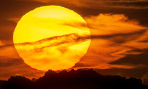 Photographer Captures Surreal Sight of Huge Raging Sun Setting Behind Iconic Rock Formation in UK
