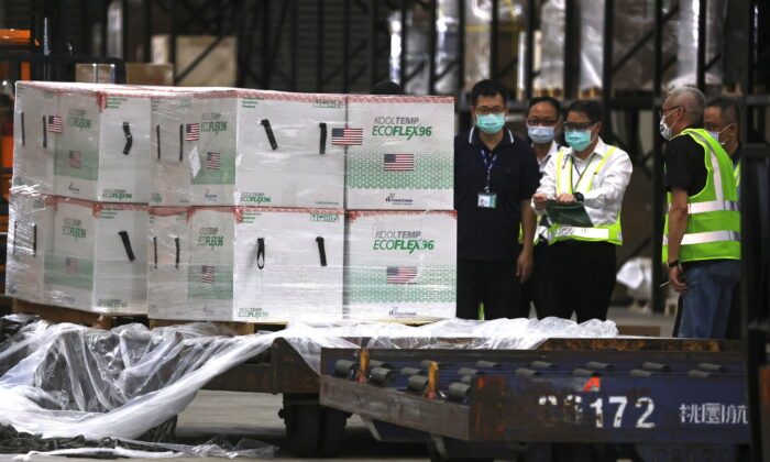 Workers transport Moderna vaccines shipped from the United States, to Taiwan Air Cargo Terminal at the Taoyuan International Airport in Taoyuan, Taiwan, on June 20, 2021. (Ann Wang/Reuters)