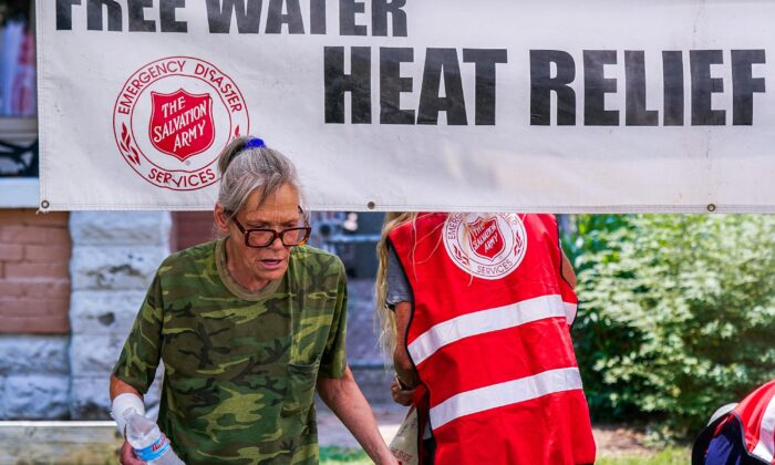 A pedestrian holds a bottle of cold water at a Salvation Army hydration station during a heatwave as temperatures hit 115 degrees F in Phoenix, on June 15, 2021. (Ross D. Franklin/File/AP Photo)