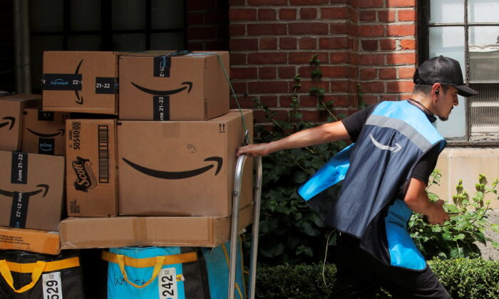 An Amazon delivery worker pulls a delivery cart full of packages during its annual Prime Day promotion in New York City, on June 21, 2021. (Brendan McDermid/Reuters)
