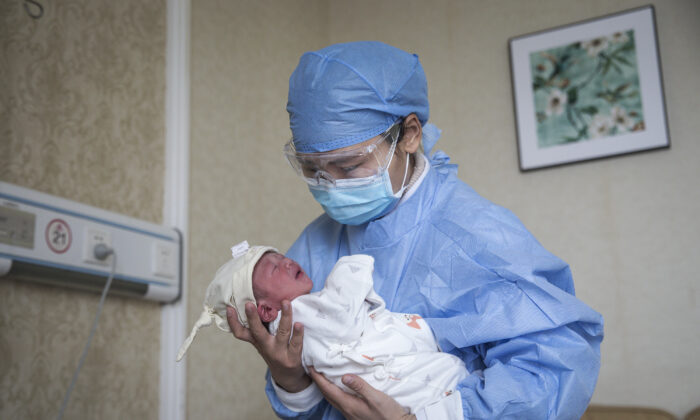 A nurse holding a baby in a private obstetric hospital in Wuhan city, Hubei Province, China, on Feb. 21, 2020. (Getty Images)