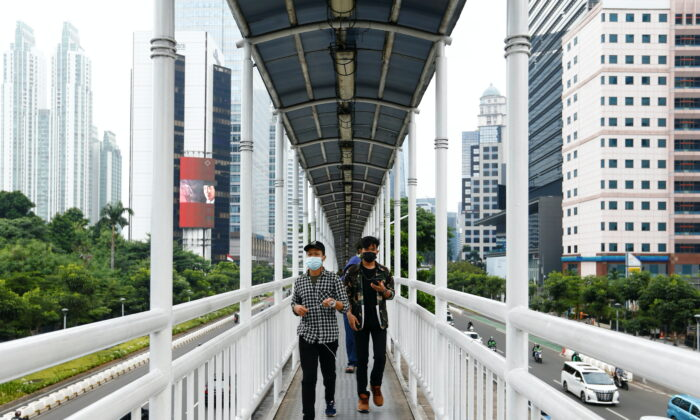 People wearing protective masks walk on a bridge in Jakarta, Indonesia, on June 17, 2021. (Ajeng Dinar Ulfiana/Reuters)