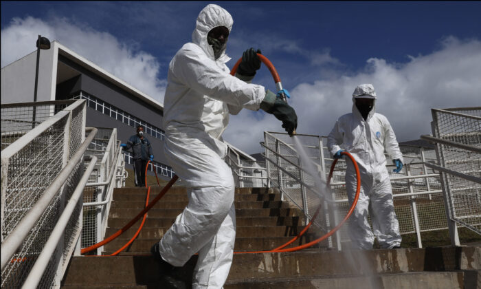 City hall employees disinfect stairs at Municipal Hospital of Parelheiros in Sao Paulo, Brazil, on June 18, 2021. (Rodrigo Paiva/Getty Images)