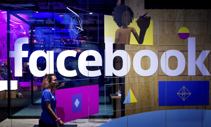 A conference worker passes a demo booth at Facebook's annual F8 developer conference, in San Jose, Calif., on April 18, 2017. (Noah Berger/AP Photo)