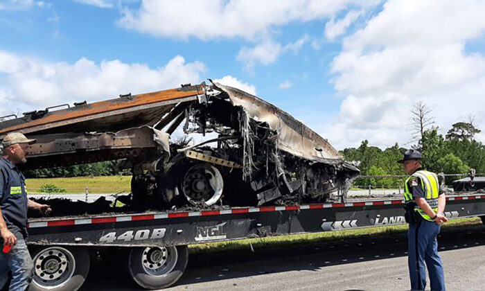 Some of the wreckage from a fatal multiple-vehicle crash a day earlier is loaded to be carried away, in Butler County, Ala., on June 20, 2021. (Lawrence Specker/Press-Register/AL.com via AP)