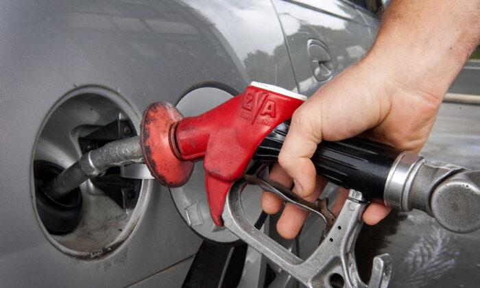 A motorist fills his car at a petrol bowser in Brisbane, Australia on June 2, 2009. (AAP Image/Dave Hunt)